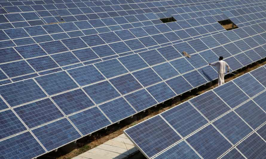 A worker cleans solar panels at the Azure solar plant in Khadoda