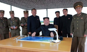 Kim Jong-Un, the chairman of the Workers' Party of Korea and supreme leader of North Korea, shares a joke with his generals after watching the launch of an intermediate-range strategic ballistic rocket Hwasong-12 at an undisclosed location near Pyongyang