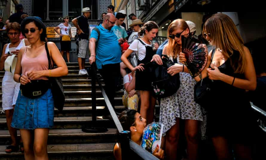 Tourists use fans as they queue in downtown Lisbon on Friday.