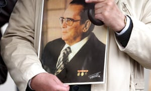 A man holds a picture of former Yugoslav president Josip Broz Tito.