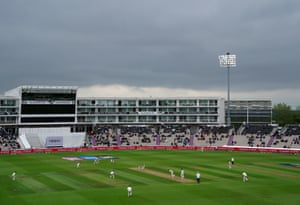 Tim Southee bowls to Virat Kohli under the lights and some dark clouds.