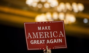 An attendee holds a 'Make America Great Again' sign up at a Trump campaign rally.