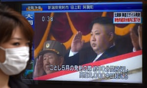 A pedestrian walks past a screen in Tokyo on 4 July broadcasting file news footage of the North Korean leader, Kim Jong-un, after a ballistic missile was launched earlier in the day