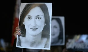 Protesters hold pictures of Daphne Caruana Galizia as they gather outside the prime ministers's office in Valletta, Malta, the day Yorgen Fenech was detained on his yacht.