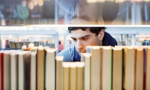 man chooses book in library
