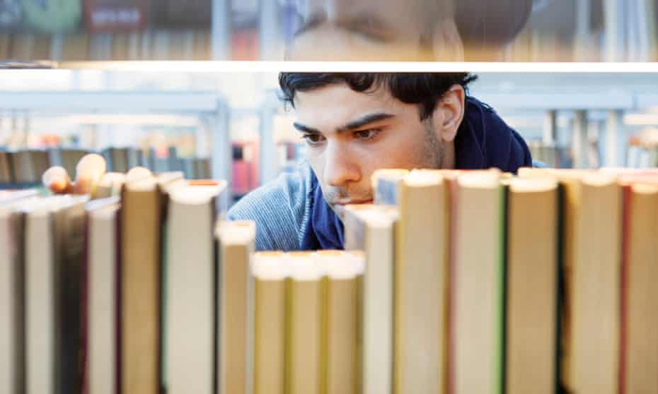 A man looks at a book in a library.