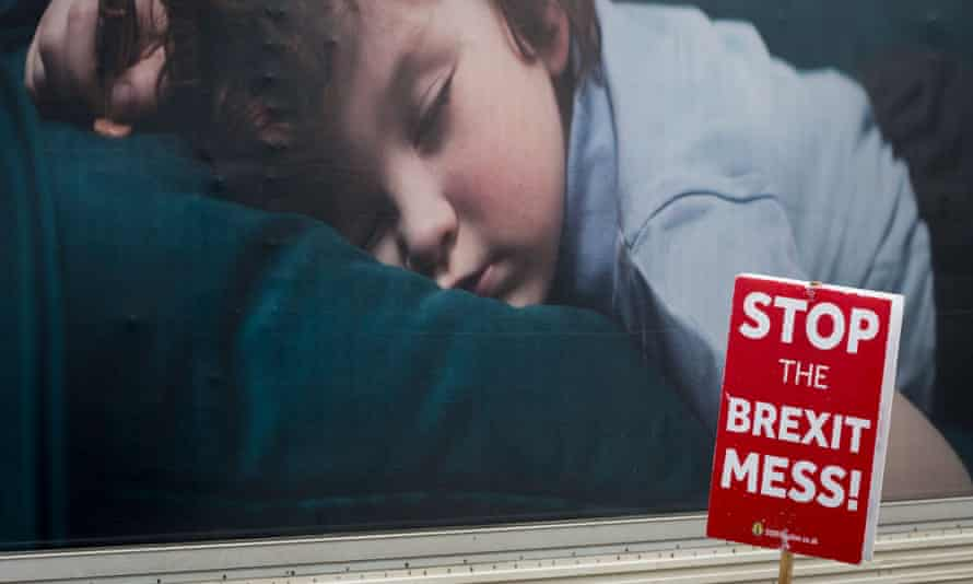 Child asleep on shoulders with 'Stop the Brexit mess now' placard