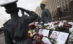 Photographs of the pilot Oleg Peshkov, left, and rescuer Alexander Pozynich at a monument to Soviet officers in Moscow