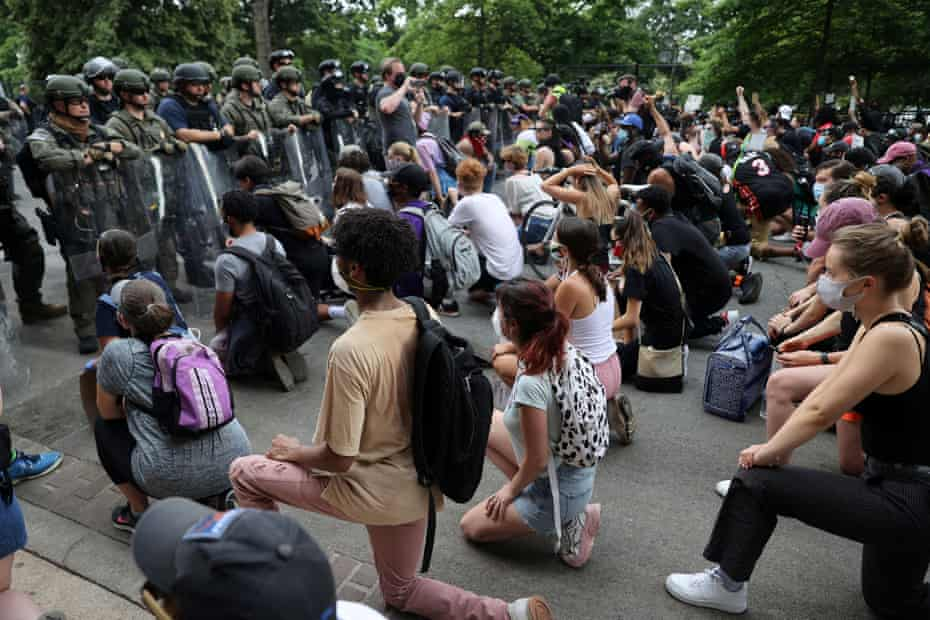Demonstrators take a knee in front of law enforcement officers during a protest against the death of George Floyd, near the White House on 3 June.