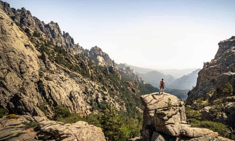 Female hiker standing on viewpoint, Aiguilles de Bavella, Corsica, France