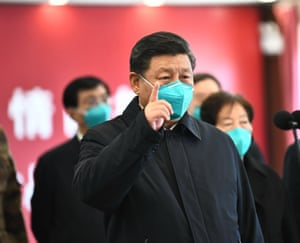 The Chinese president, Xi Jinping, wears a mask as he gestures to a coronavirus patient and medical staff via a video link with Huoshenshan hospital in Wuhan