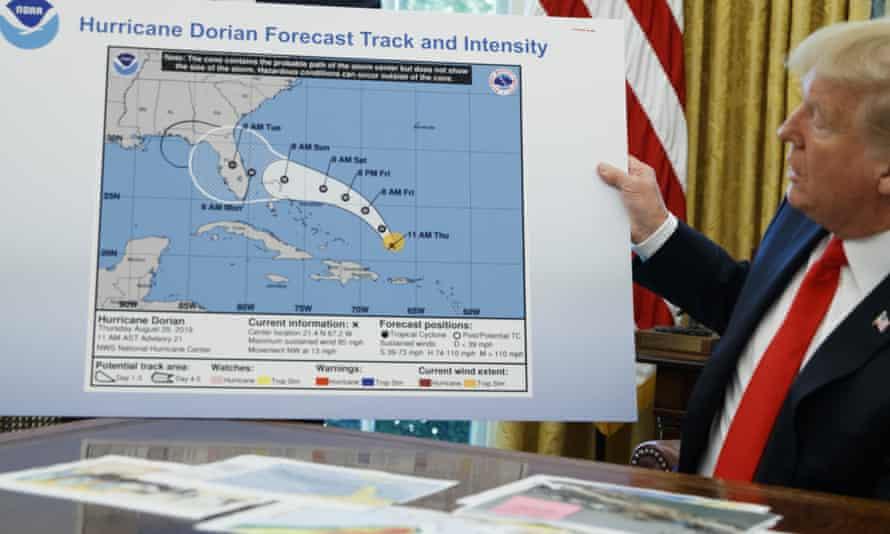 Donald Trump holds a chart showing Hurricane Dorian