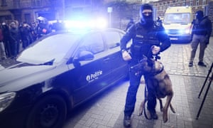Police and dogs block the road after the raid in the Rue des Quatre-Vents, Molenbeek