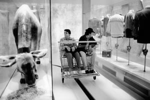 A couple, seated in a maxi shopping cart, looks at the exhibits of a dairy cow eating hay and clothes displayed on dress stands.