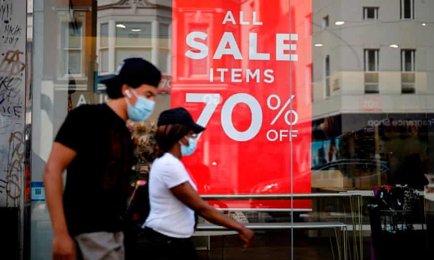 Shoppers wearing face masks walk past sales signs in the window of a shop in London on August 12, 2020.