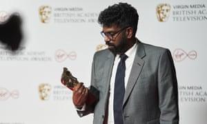 Romesh Ranganathan studies his award at the Virgin Media British Academy Television Awards, Winners Press Room.