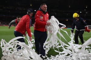 Staff clear streamers thrown onto the pitch.