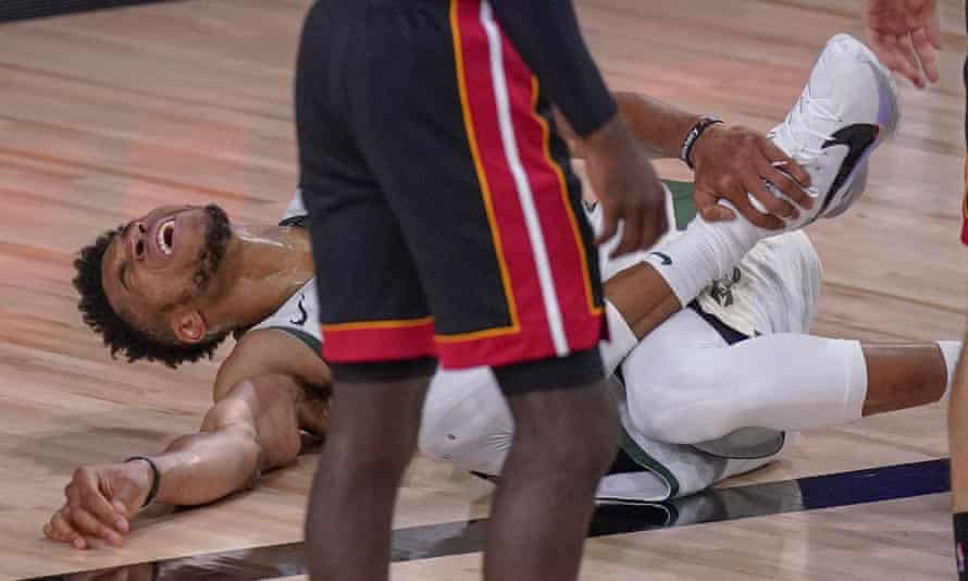 Giannis Antetokounmpo reacts after hurting his ankle during the first half