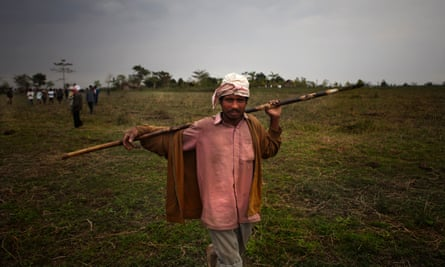 Armed with a makeshift spear, an Assam man sets out to chase away the elephant that crushed a woman to death in the village of Galighat.