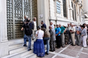 People wait to enter a bank branch in Athens this morning.