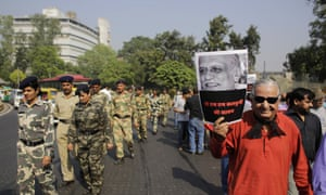 An Indian writer holds a portrait of Malleshappa Kalburgi, an award-winning writer murdered in August for his writings against superstition and false beliefs, as part of a protest in New Delhi last month.