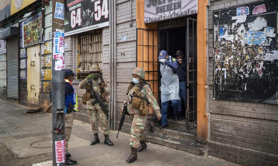 South African police search a local bar in downtown Johannesburg in March