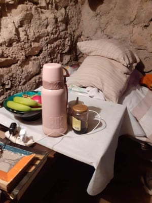 Bedding and a small table holding power cables, a pink flask and a bowl of fruit beside an earthen wall