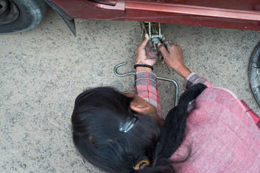 Hemlata changes a flat tire as part of a professional driving workshop.