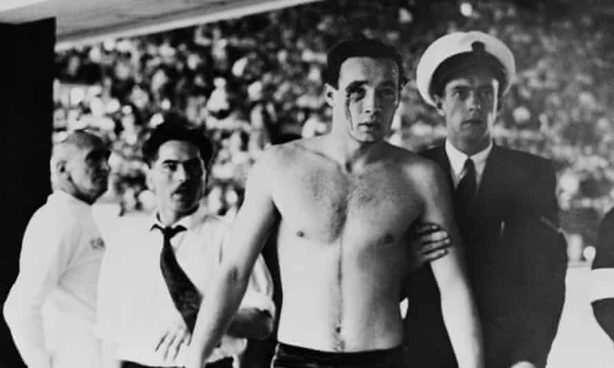 Hungary's Ervin Zador is escorted from the pool with blood pouring from his cut eye during their 1956 Olympic water polo win over Russia.