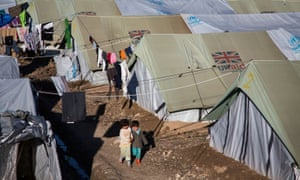 Children walk through a camp in northern Iraq housing people displaced by Isis attacks