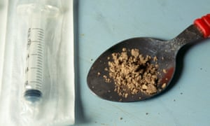 spoon with heroin in it with a syringe alongside