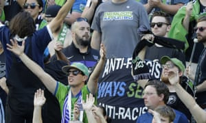 A sign that reads 'Anti-Facist Always Seattle Anti-Racist' is displayed in the supporters section during an MLS match between the Sounders and the Timbers in Seattle