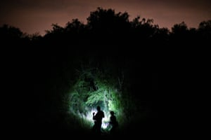 Border patrol agents search for undocumented migrants who have illegally crossed the Rio Grande from Mexico into Texas.