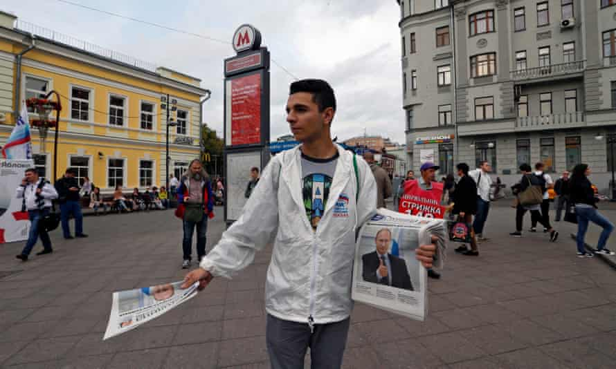 A United Russia supporter hands out newspapers in Moscow.