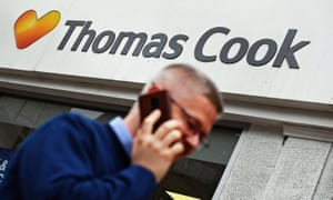 A pedestrian passes a Thomas Cook travel store in London.