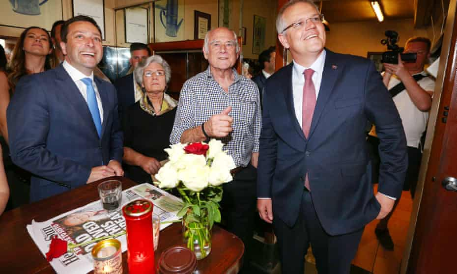Pellegrini's co-owner Nino Pangrazio shows off photographs to Victorian opposition leader Matthew Guy (L) and prime minister Scott Morrison as the coffee house reopens to the public after the deadly Bourke Street attack, in which co-owner Sisto Malaspina was killed.