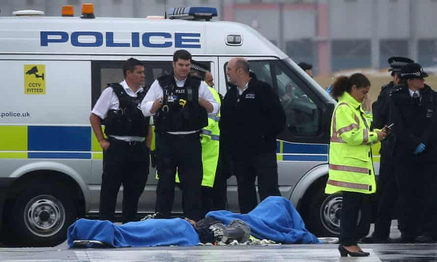 Police surround the last two remaining protesters  occupying the north runway at Heathrow airport on 13 July 2015
