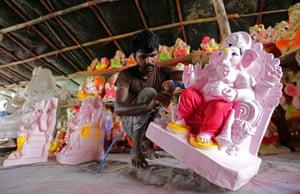 An artist paints a cast of the Hindu elephant-headed god Ganesha in Amritsar, India