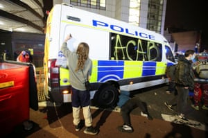 A demonstrator graffitis a police vehicle.