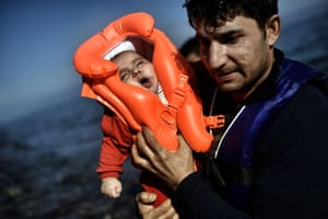 Lesbos, Greece A father carries his baby to shore after crossing the Aegean Sea from Turkey in a dinghy