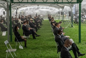 People sit in distanced chairs at the ceremony