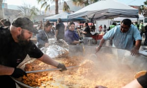 Volunteers cook paella in a huge pan for the migrants staying at El Baterral shelter in Tijuana, Mexico on 23 December.