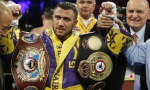 Vasiliy Lomachenko displays his title belts after retaining his WBA and WBO lightweight titles.