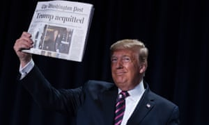Donald Trump holds up a copy of the Washington Post with the headline 'Trump Acquitted'