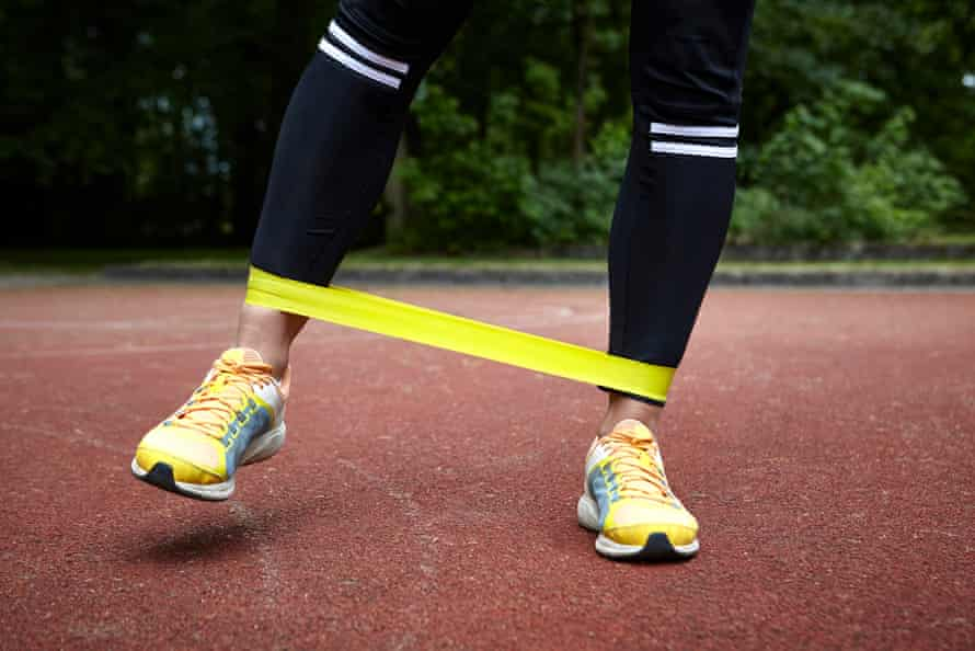 The feet and legs of someone training with a resistance band around their ankles