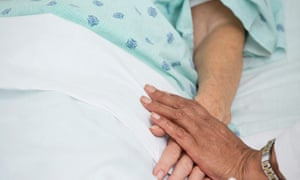 doctor holding patient's hand in hospital