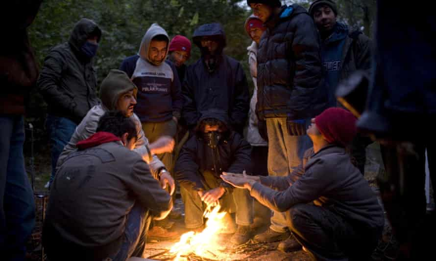Migrants warm themselves by a campfire at their camp in the Grande-Synthe woods near Calais.