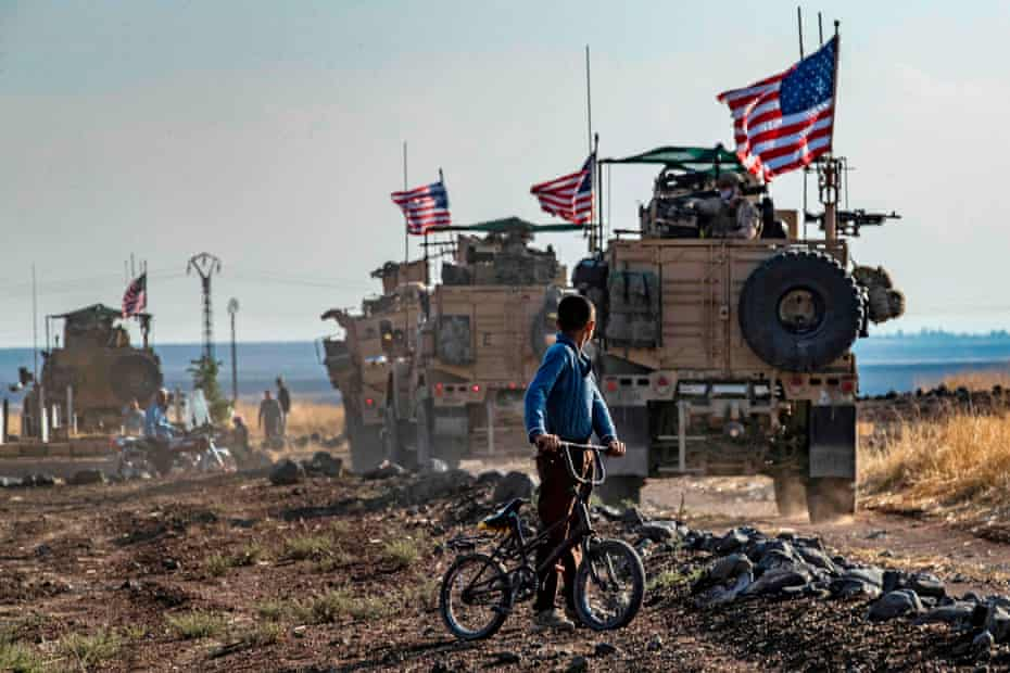 A Syrian boy on his bicycle looks at a convoy of US armoured vehicles patrolling fields near the town of Qahtaniyah, at the border with Turkey, 31 October