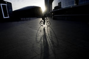 Milan, ItalyA man rides a bike in the early morning at the Porta Nuova business center in Milan.