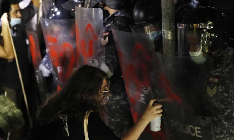 """A supporter of relatives of people who were killed in last year's massive blast at Beirut's seaport, left, sprays the word """"Revolution"""" in Arabic on the shields of riot police."""
